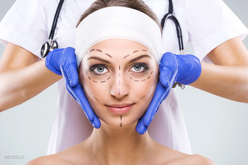 Female on plastic surgery office with marked lines on face