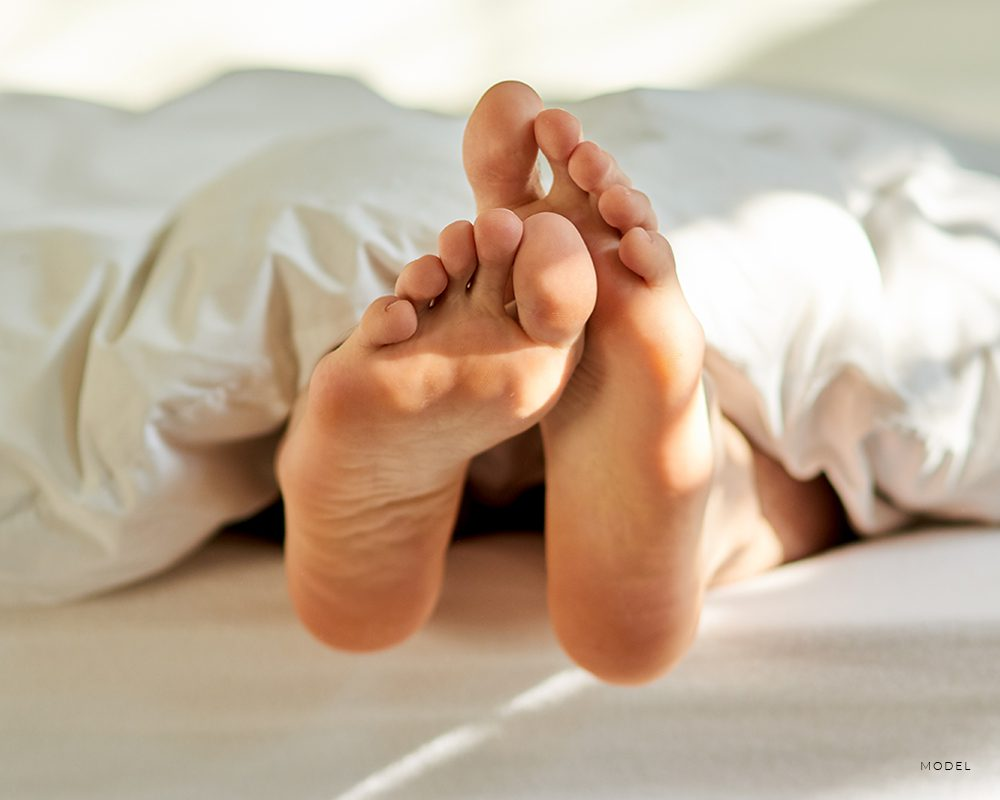 Feet Coming Out Of A White Bed Cover