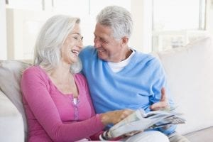 Mature Couple Looking at a Magazine and Smiling
