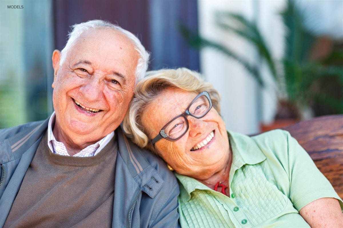 Old Couple Leaning Against Each Other on Couch
