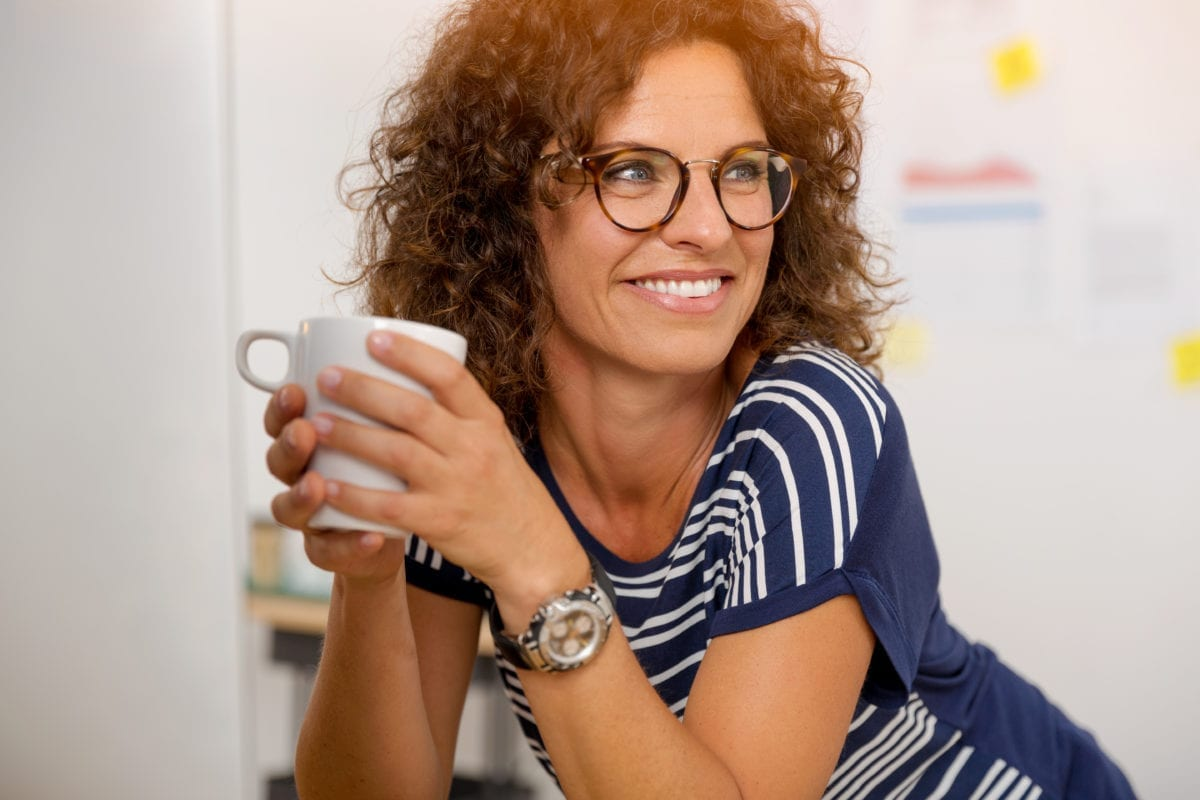Older Female Wearing Glasses and Holding a Mug