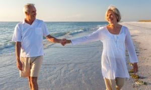 Mature Couple holding hands while walking on the beach